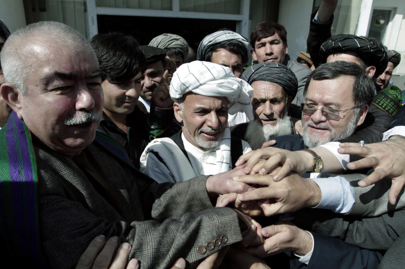 Ashraf Ghani, former Afghan finance minister, center, joins hands with his supporters after registering his candidacy in next year's presidential election at the independent election commission office in Kabul, Afghanistan, Sunday, Oct. 6, 2013. A slew of political heavyweights, along with the Afghan president's brother and a number of former warlords, will take part in next year's elections for the country's top office in a critical vote that could determine the future course of the country and the level of foreign involvement in Afghanistan after 12 years of war. (AP Photo/Rahmat Gul)