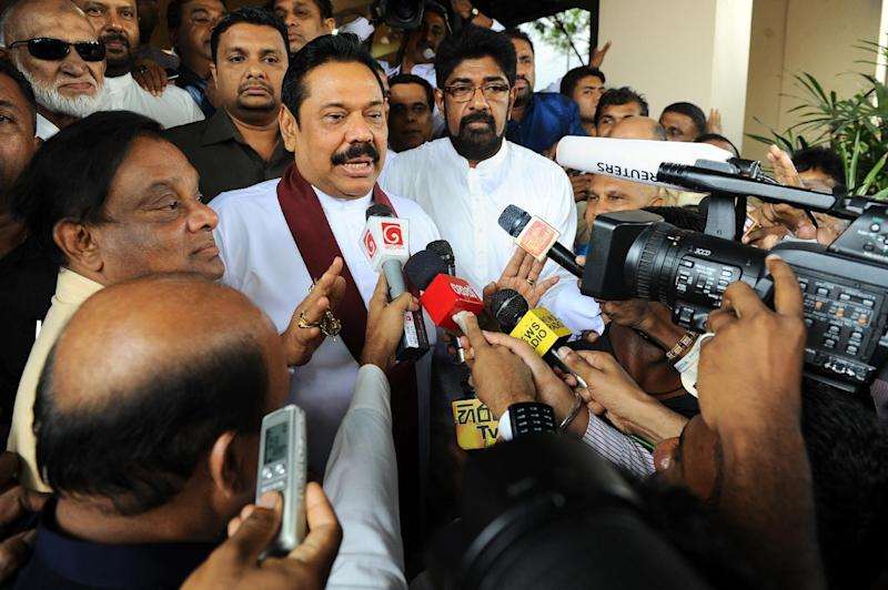 Sri Lankan President Mahinda Rajapakse (C) speaks to journalists in Colombo on December 8, 2014 after handing in his nomination papers for the January polls