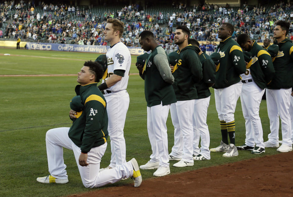 """FILE - In this Sept. 23, 2017, file photo, Oakland Athletics catcher Bruce Maxwell kneels during the national anthem before the team's baseball game against the Texas Rangers in Oakland, Calif. Maxwell is the only major leaguer to take a knee during the playing of """"The Star-Spangled Banner"""" before a game. Major leaguers have not, in general, been the first set of players in pro sports to speak out on issues of social injustice. We'll see what stances they take on and off the field when games return. (AP Photo/Eric Risberg, File)"""