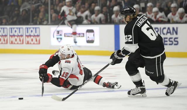 Ottawa Senators left wing Zack Smith, left, falls as he tries to pass the puck while under pressure from Los Angeles Kings left wing Carl Hagelin during the first period of an NHL hockey game Thursday, Jan. 10, 2019, in Los Angeles. (AP Photo/Mark J. Terrill)