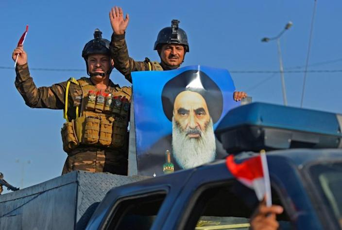 Iraqi security forces parade a portrait of Sistani as they patrol the Shiite holy city of Najaf where he is based (AFP Photo/Haidar HAMDANI)