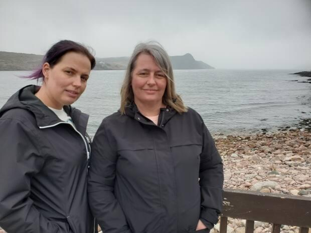 Amy Doyle and her daughter, Kerri Lynn Kettle, stand over the site on a beach in St. Lawrence where Doyle hopes to establish a fishermen's memorial.  (Jane Adey/CBC - image credit)
