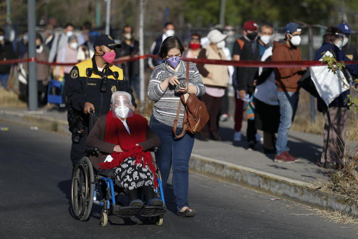 A police officer pushes an elderly woman in a wheelchair to the front of the line as residents of the Iztacalco borough over age 60 wait to get shots of the Sputnik V vaccine for COVID-19 at a vaccination center set up at the Advanced School for Physical Education in Mexico City, Wednesday, Feb. 24, 2021. (AP Photo/Rebecca Blackwell)