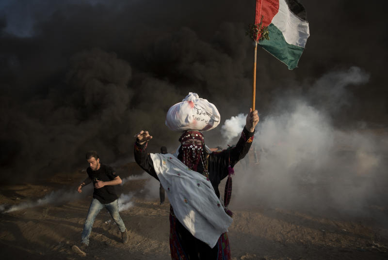 Palestinian protesters run for cover from teargas fired by Israeli troops during a protest at the Gaza Strip's border with Israel, Friday, Oct. 12, 2018. (AP Photo/Khalil Hamra)