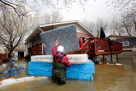 Jean-Francois Perrault (C) and Julie Theriault (L) move mattresses from a home in a flooded residential area in Gatineau, Quebec, Canada, May 7, 2017. REUTERS/Chris Wattie