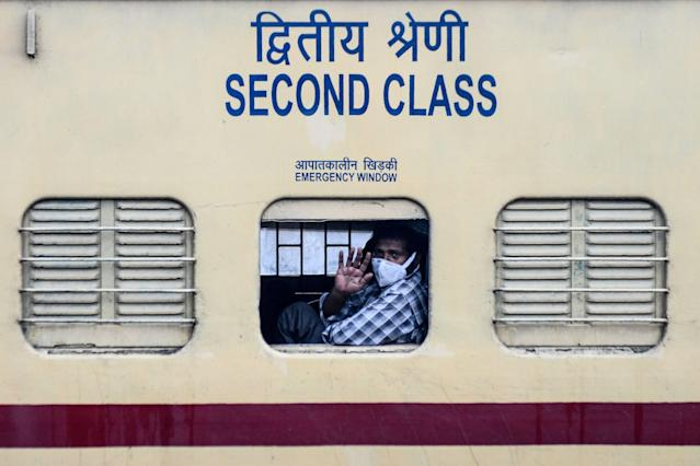 A migrant worker waves from the window of a special train going to Gorakhpur in Uttar Pradesh state back to his hometown after the government eased a nationwide lockdown imposed as a preventive measure against the COVID-19 coronavirus, in Amritsar on May 14, 2020. (Photo by NARINDER NANU / AFP) (Photo by NARINDER NANU/AFP via Getty Images)