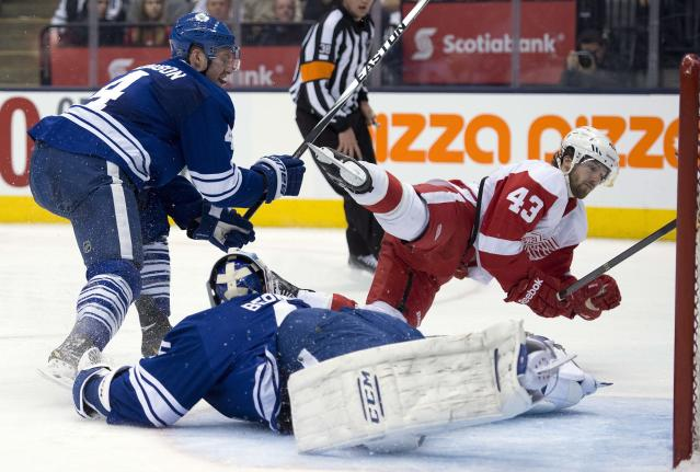Detroit Red Wings center Darren Helm (43) completes his hat trick with a goal past Toronto Maple Leafs goaltender Jonathan Bernier and defenseman Cody Franson in NHL hockey game action in Toronto, Saturday, March 29, 2014. (AP Photo/The Canadian Press, Frank Gunn)