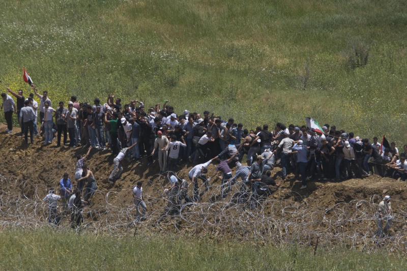 Pro Palestinians protesters try to break a fence along the border between Israel and Syria near the village of Majdal Shams in the Golan Heights, Sunday, June 5, 2011 . Israeli troops opened fire across the Syrian frontier on Sunday to disperse hundreds of pro-Palestinian protesters who stormed the border of the Israeli-controlled Golan Heights, reportedly killing four people in unrest marking the anniversary of the Arab defeat in the 1967 Mideast war. (AP Photo/Ariel Schalit)