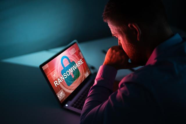 Worried Businessman Looking At Laptop With Ransomware Word On The Screen At The Workplace