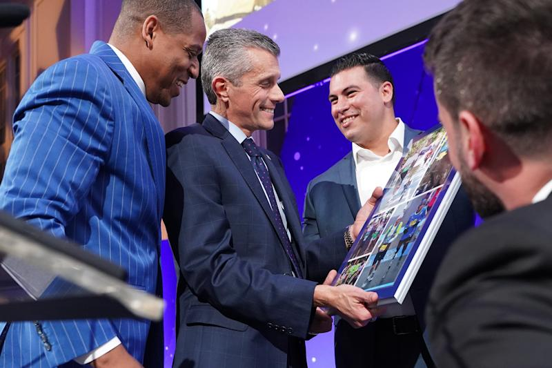 Achilles International Freedom Team members, Cedric King, Stefan LeRoy and Matias Ferreira, present the Volunteer of the Year award to David Cordani, President and CEO of Cigna.