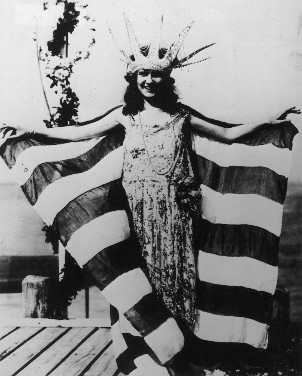 <p>Miss America's evening gown competition has been iconic since the very first pageant. Margaret Gorman from Washington D.C.'s look is proof: She wore a drop waist embroidered gown and topped it off with an American flag shawl.</p>