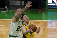 Indiana Pacers guard T.J. McConnell (9) goes to the hoop against Boston Celtics center Daniel Theis (27) in the first quarter of an NBA basketball game, Friday, Feb. 26, 2021, in Boston. (AP Photo/Elise Amendola)