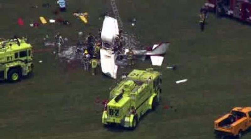This frame grab from video provided by WDIV, WJBK, and WXYZ, shows emergency personnel examining a plane crash after a pilot and three passengers were killed shortly after takeoff from an airport northwest of Detroit in Waterford Township, Mich., on Friday, June 21, 2013. Three people aboard the private flight were killed instantly, while the fourth died later at a hospital. (AP Photo/WDIV, WJBK, & WXYZ)
