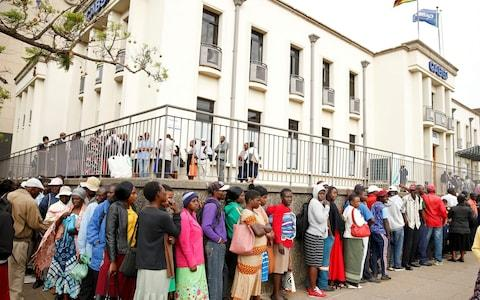 People queue to withdraw money in Harare after Zimbabwe introduced a new currency - Credit: REUTERS/Philimon Bulawayo
