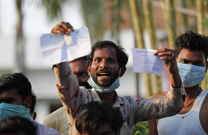 A laborer displays his identification as he protests against poor treatment at the quarantine center he has been kept in, along with others who arrived from outside the state, in Prayagraj, India, Wednesday, April 29, 2020, amid shelter-in-place orders. (AP Photo/Rajesh Kumar Singh)