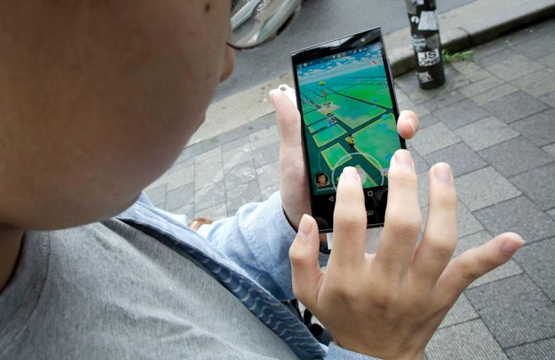 """A man maneuvers his smartphone as he plays """"Pokemon Go"""" at Akihabara in Tokyo, Friday, July 22, 2016. Users began tweeting it as soon as it was available Friday morning, and the Pokemon Co. and the developer of the augmented reality game, U.S.-based Niantic Inc., confirmed its launch shortly after. (AP Photo/Eugene Hoshiko)"""