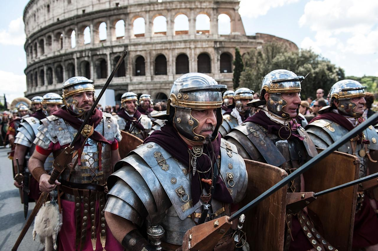 ROME, ITALY - APRIL 21: Actors dressed as ancient Roman soldiers march in front of the Coliseum in a commemorative parade during festivities marking the 2,766th anniversary of the founding of Rome on April 21, 2013 in Rome, Italy. The capital celebrates its founding annually based on the legendary foundation of the Birth of Rome. Actors dressed as the denizens of ancient Rome participate in parades and re-enactments of the ancient Roman Empire. According to legend, Rome had been founded by Romulus in 753 BC in an area surrounded by seven hills. (Photo by Giorgio Cosulich/Getty Images)