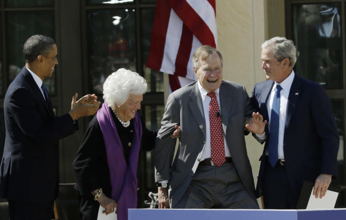 <p>As President Barack Obama applauds at left, former first lady Barbara Bush and former President George W. Bush help former President George H.W. Bush stand to acknowledge a standing ovation during the dedication of the George W. Bush Presidential Center on April 25, 2013, in Dallas. (Photo: David J. Phillip/AP) </p>