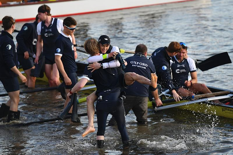 The Oxford cox Sam Collier is lifted up and embraced by a team member after winning the annual men's boat race on the River Thames in London on April 2, 2017 (AFP Photo/Ben STANSALL)