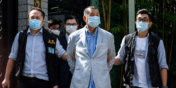 Police lead Hong Kong pro-democracy media mogul Jimmy Lai from his home after he was arrested under the new national security law in Hong Kong on August 10, 2020