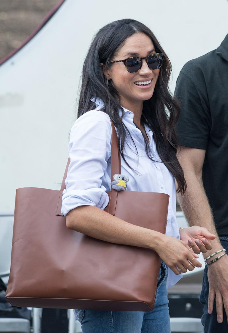 """At the Games, Markle sported a <a href=""""https://www.huffingtonpost.ca/entry/meghan-markle-husband-shirt_ca_5cd5072be4b07bc729741427"""" target=""""_blank"""" rel=""""noopener noreferrer"""">white button-up shirt</a> by her friend Misha Nonoo and ripped skinny jeans with an oversized Everlane tote."""