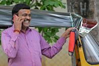 A driver in Hyderabad hangs his mask on the wing mirror as he talks on the phone (AFP Photo/NOAH SEELAM)