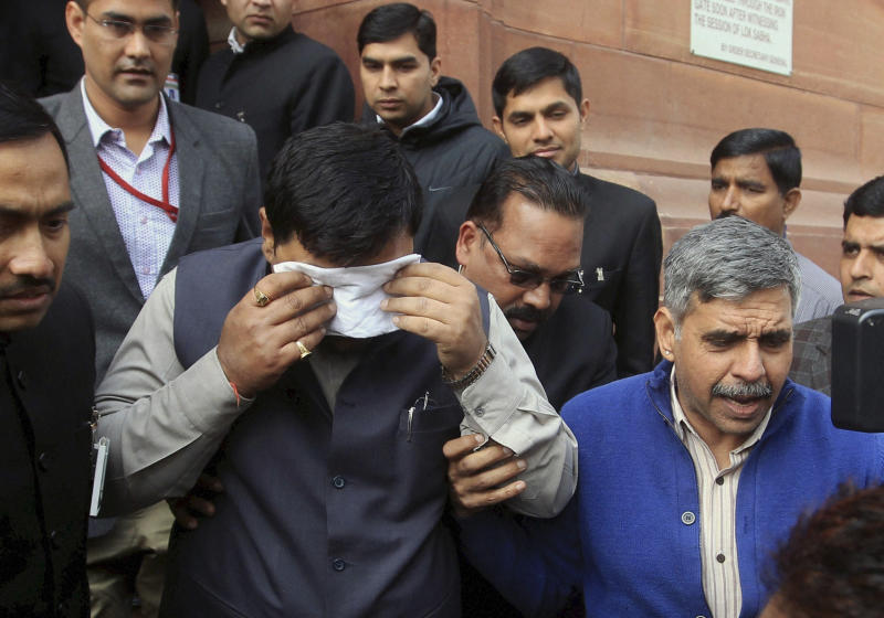 An unidentified member of India's parliament covers his face with a handkerchief after being affected by pepper spray gas in New Delhi, India, Thursday, Feb. 13, 2014. Congress party lawmaker L. Rajagopal from Andhra Pradesh sprayed pepper spray inside the parliament from the main speaking zone, creating chaos that left his colleagues coughing and crying as they were ushered from the hall, in a protest over a long-contentious proposal to create a new southern state of Telangana from the existing Andhra Pradesh state. (AP Photo)