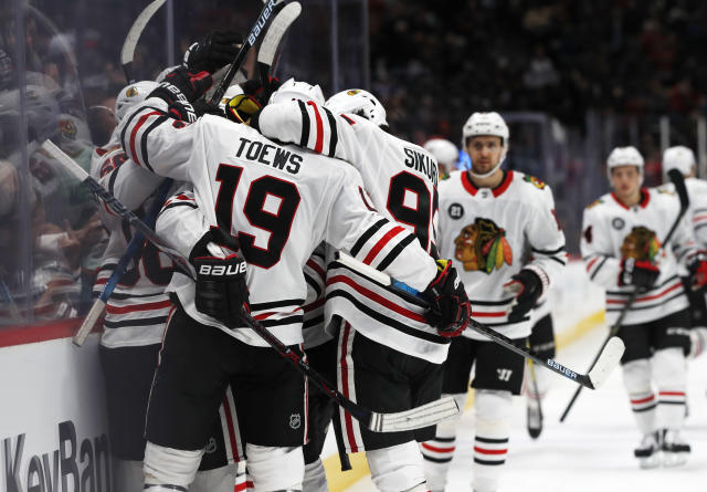 Chicago Blackhawks right wing Patrick Kane is enveloped by teammates, including Jonathan Toews and Dylan Sikura, after Kane scored in overtime of an NHL hockey game Saturday, Dec. 29, 2018, in Denver. The Blackhawks won 3-2. (AP Photo/David Zalubowski)
