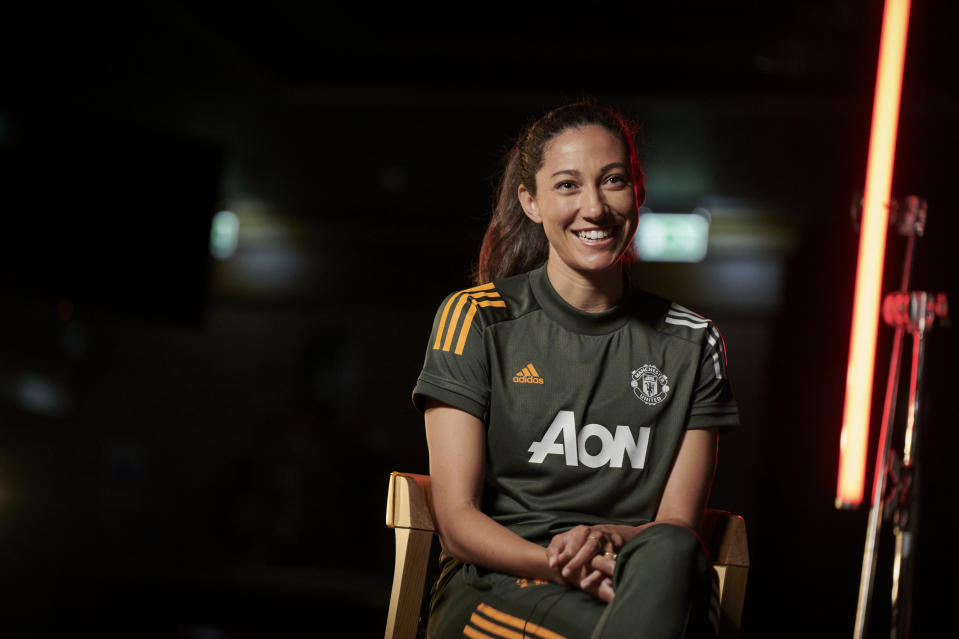 Christen Press in a black Manchester United kit sits on a chair.