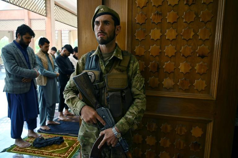 An Afghan security worker stands guard as Muslim devotees offer prayers to start the Eid-al-Fitr festival at a mosque in Kabul