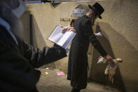 An ultra-Orthodox Jewish man holds a chicken as part of the Kaparot ritual, in Bnei Brak, Israel, Sunday, Sept. 27, 2020. Observant Jews believe the ritual transfers one's sins from the past year into the chicken, and is performed before the Day of Atonement, Yom Kippur, the holiest day in the Jewish year which starts at sundown Sunday. The solemn Jewish holiday of Yom Kippur, which annually sees Israeli life grind to a halt, arrived on Sunday in a nation already under a sweeping coronavirus lockdown. (AP Photo/Oded Balilty)