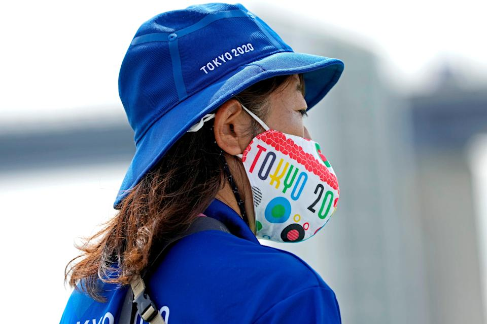 A volunteer with a Tokyo 2020 mask looks on at the rowing venue during the Tokyo 2020 Olympic Summer Games at Sea Forest Waterway.