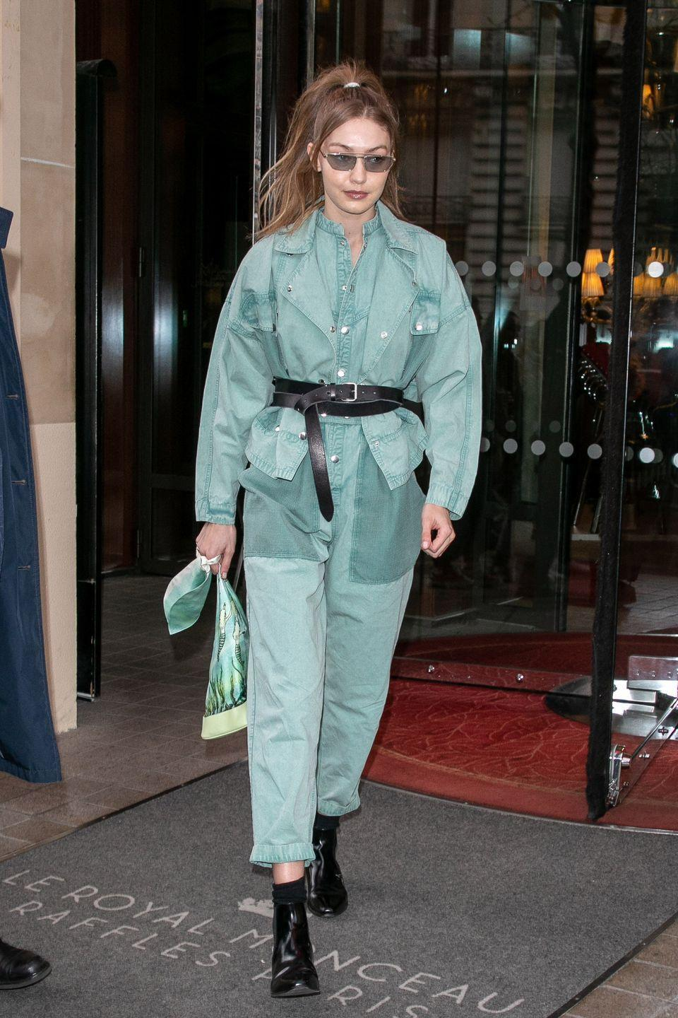 <p>In an oversized green jumpsuit, black ankle boots, black waist-cinching belt, and sunglasses. </p>