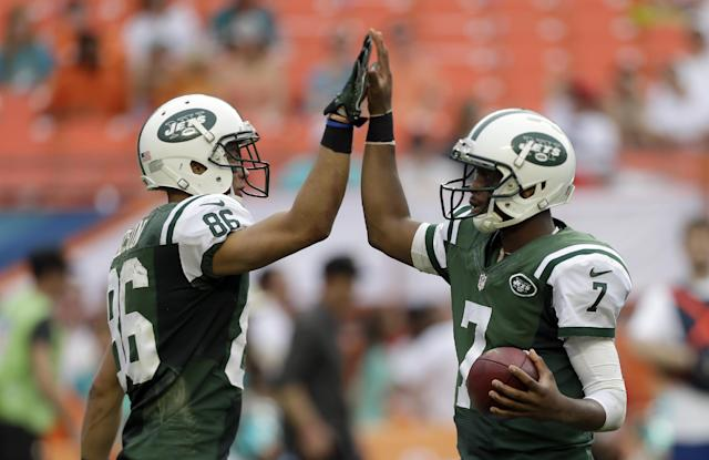 New York Jets quarterback Geno Smith (7) gives a high-five to teammate David Nelson (86) before the last play against the Miami Dolphins in the fourth quarter of a NFL football game in Miami Gardens, Fla., Sunday, Dec. 29, 2013. The Jets won 20-7. (AP Photo/Alan Diaz)