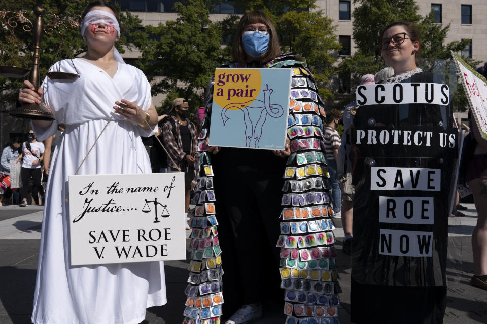 Activists hold signs during the Women's March rally at Freedom Plaza, in Washington, Saturday, Oct. 2, 2021. (AP Photo/Jose Luis Magana)