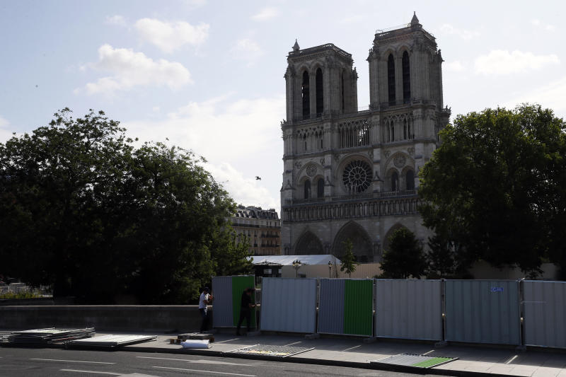 Workers install high fences on a bridge around Notre Dame cathedral in Paris, Tuesday, Aug. 13, 2019. Workers are preparing to decontaminate some Paris streets surrounding the Notre Dame Cathedral that have been tested with high levels of lead following the April blaze that damaged the landmark. (AP Photo/Francois Mori)
