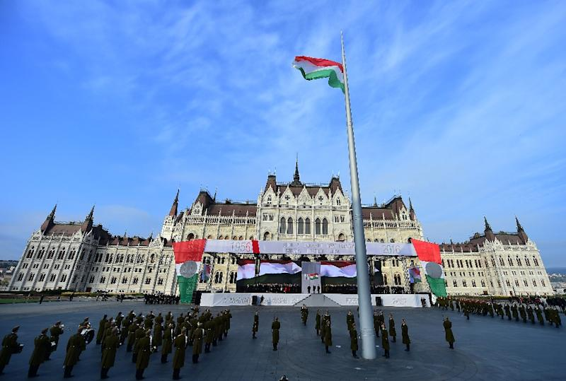 Soldiers of the Hungarian honour guard present the national flag in front of the parliament building, during a ceremony to mark the 60th anniversary of 1956 anti-Soviet uprising in Budapest on October 23, 2016