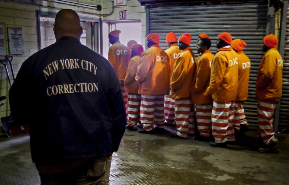 FILE - In this March 16, 2011 file photo, a corrections official watches inmates file out of a prison bakery after working the morning shift at the Rikers Island jail in New York. New York City's notorious Rikers Island jail complex, troubled by years of neglect, has spiraled into turmoil during the coronavirus pandemic. (AP Photo/Bebeto Matthews, File)