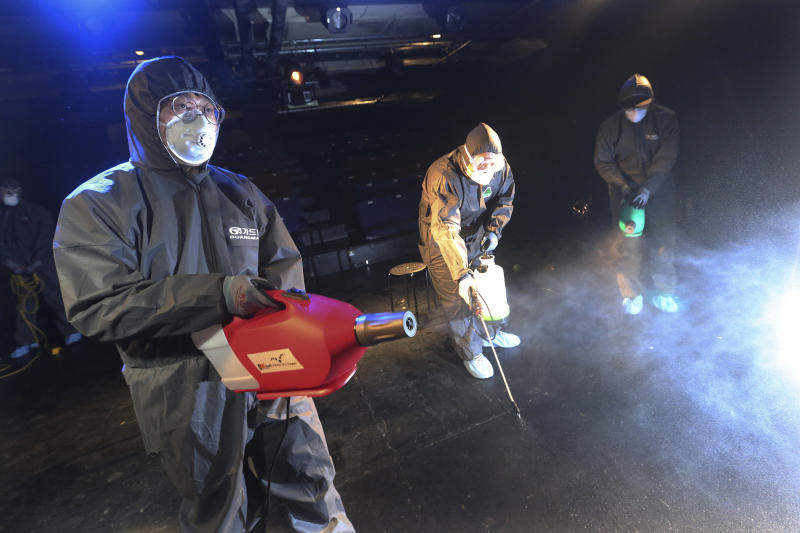 Workers wearing protective gears spray disinfectant as a precaution against a new coronavirus at a theater in Seoul, South Korea, Thursday, Feb. 6, 2020. Ten more people were sickened with a new virus aboard one of two quarantined cruise ships with some 5,400 passengers and crew aboard, health officials in Japan said Thursday, as China reported 73 more deaths and the World Health Organization appealed for more funds to help countries battle the spread of the disease. (AP Photo/Ahn Young-joon)