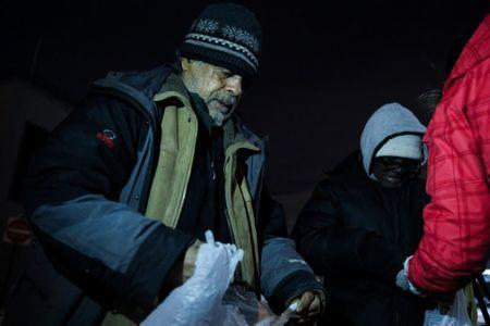 People receive food from the New York City's Coalition for the Homeless as they deliver food, donated clothing and supplies to homeless people as part of their weekly distribution during winter storm Grayson in Manhattan, New York City, U.S., January 4, 2018. REUTERS/Amr Alfiky