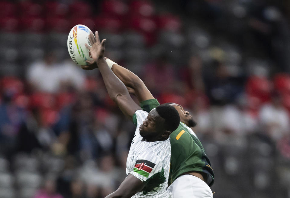 Kenya's Levy Amunga, left, and South Africa's Darren Adonis vie for the ball during an HSBC Canada Sevens rugby game in Vancouver, British Columbia, Saturday, Sept. 18, 2021. (Darryl Dyck/The Canadian Press via AP)