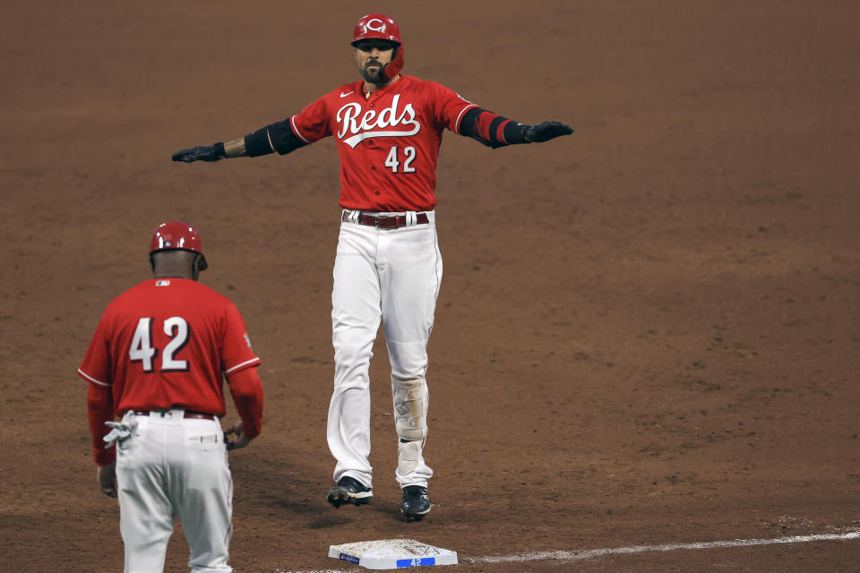 Cincinnati Reds' Nick Castellanos reacts to hitting an RBI single during the third inning of a baseball game against the Cleveland Indians in Cincinnati, Friday, April 16, 2021. (AP Photo/Aaron Doster)