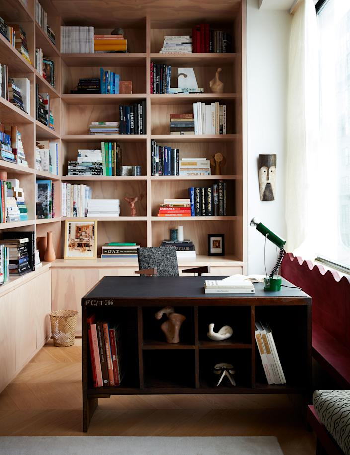 Valle lined a corner of the living room with bookshelves. Pierre Jeanneret desk; André Sornay desk chair from Donzella, and 1970s Italian desk lamp from George Champion. The metal wastebasket is by Mathieu Matégot, and a photograph of Yves Saint Laurent's office by Gilles Bensimon sits on a shelf behind the desk.