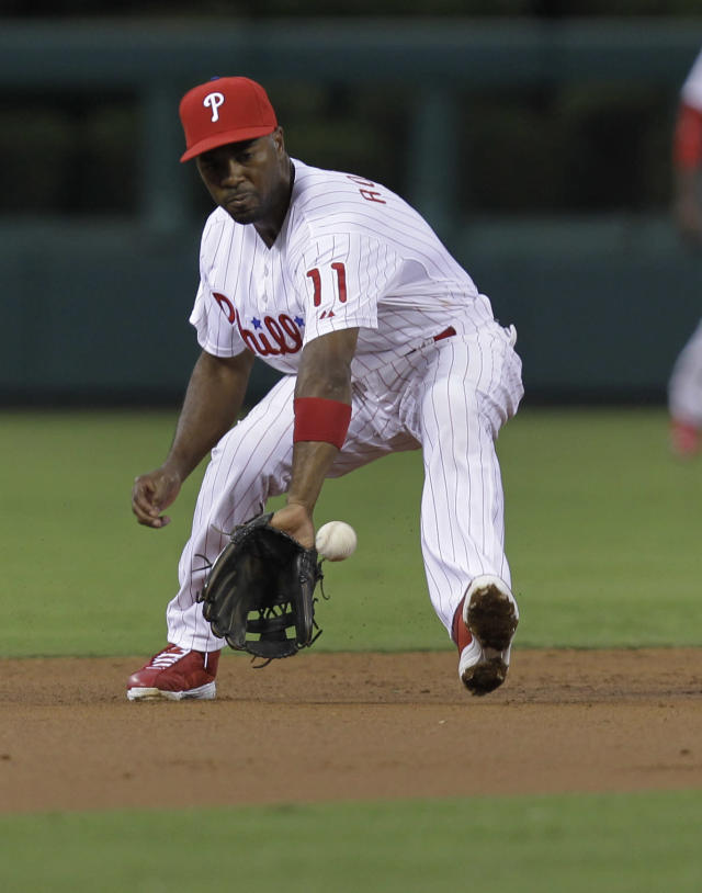 Philadelphia Phillies shortstop Jimmy Rollins fields a grounder by Colorado Rockies' Dexter Fowler in the third inning of a baseball game, Monday, Aug. 19, 2013, in Philadelphia. (AP Photo/Laurence Kesterson)