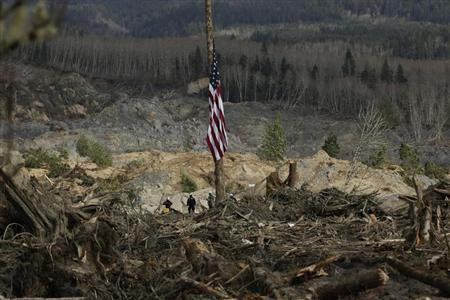 A flag flies at half staff as workers look out over the mud and debris as search work continues from a massive mudslide that struck Oso near Darrington