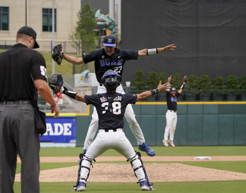 Duke pitcher Marcus Johnson, center top, celebrates with catcher Michael Rothenberg after their win over North Carolina State in an NCAA college baseball game during the Atlantic Coast Conference championship game on Sunday, May 30, 2021, in Charlotte, N.C. (AP Photo/Chris Carlson)