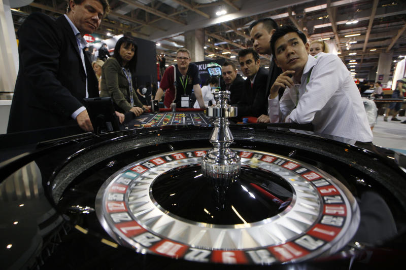 FILE - Staff members of the Gaming Expo Asia sit at a roulette table during the trade show and conference for the Asian gaming market in Macau on Tuesday, May 22, 2012. (AP Photo/Kin Cheung)