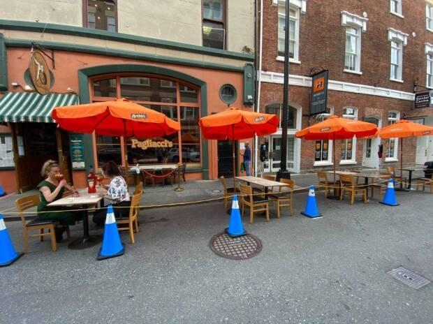 A diner enjoys a cold beverage on a summer day in 2020 at Pagliacci's Restaurant's pop-up patio.