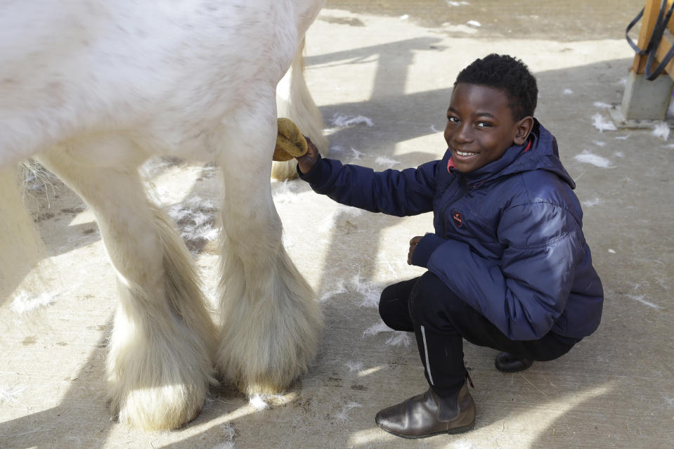Shaddai Mcleod, 9, washes the legs of Rose at Ebony Horse Club in Brixton, south London, Sunday, April 18, 2021. In the midst of south London's hustle and bustle, only a 10-minute walk from a subway station, is a school where children are encouraged to horse around. The Ebony Horse Club provides 140 rides per week to children in the local community offering them the opportunity to learn important life skills along with horseback riding. (AP Photo/Kirsty Wigglesworth)