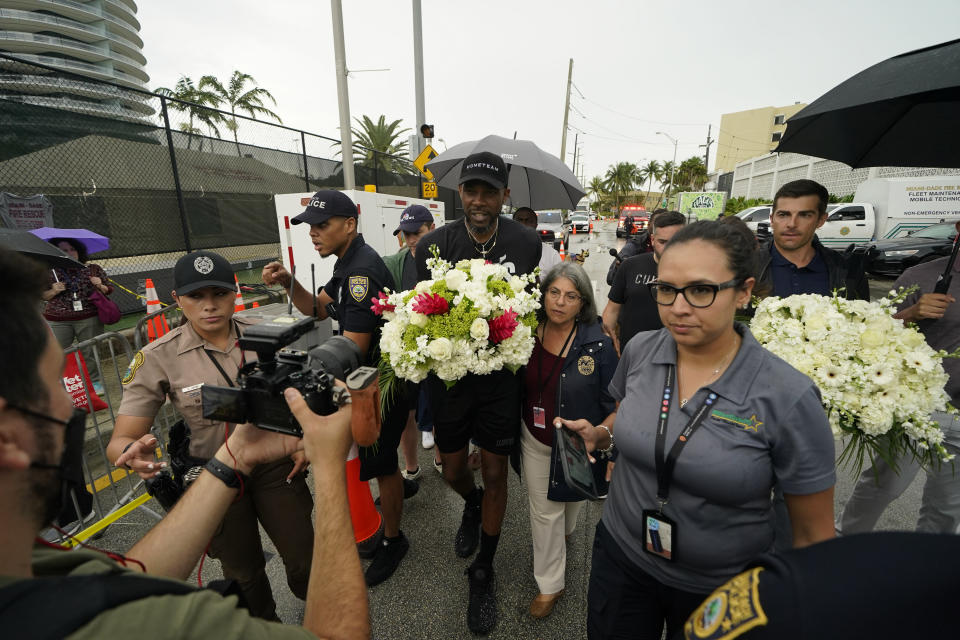 Miami Heat forward Udonis Haslem, carrying flowers, walks with his arm around Miami-Dade County Mayor Daniella Levine Cava as he arrives to pay his respects at a makeshift memorial to the people who were killed and the scores who remain missing, nearly a week after the partial collapse of the Champlain Towers South condo building, Wednesday, June 30, 2021, in Surfside, Fla. (AP Photo/Gerald Herbert)